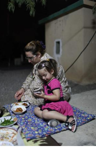 Nayman Haldar and her three-year-old daughter, Hannan, share a meal at the checkpoint PHOTO: Anastasia Taylor-Lind